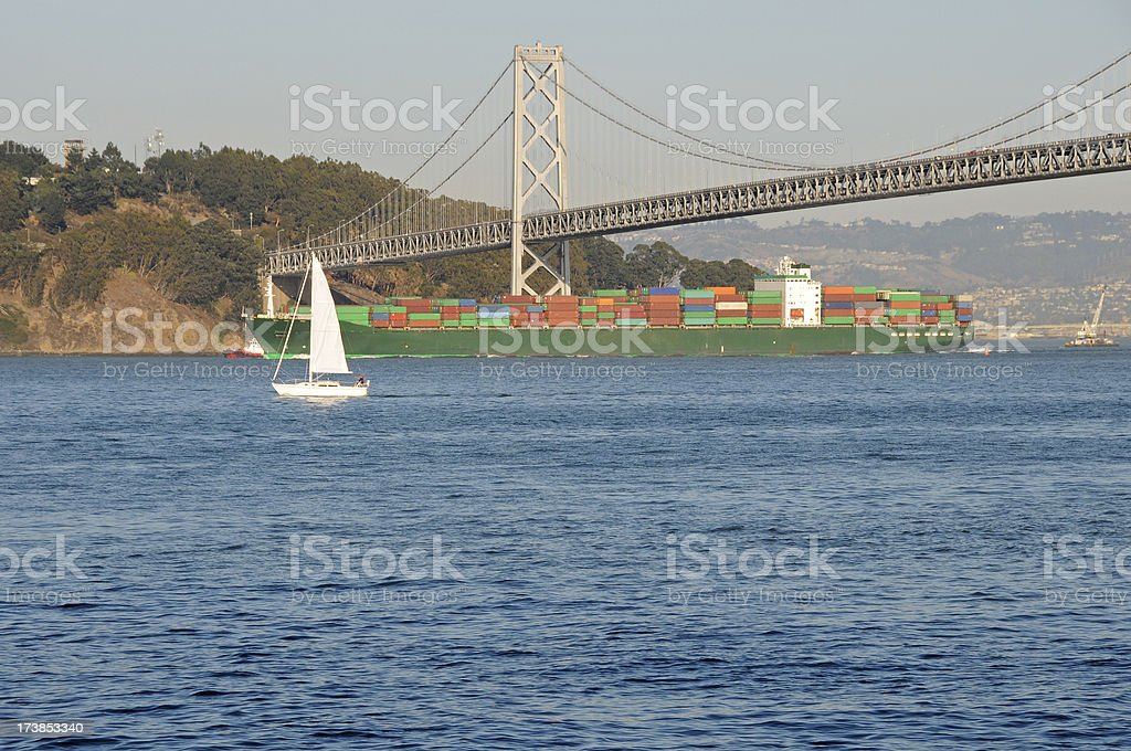 Sailboat and freighter under Bay Bridge in San Francisco royalty-free stock photo