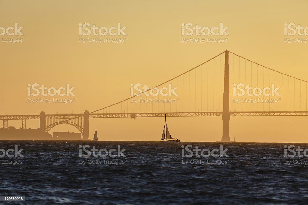 Sailboat and Golden Gate Bridge on horizon at sunset royalty-free stock photo