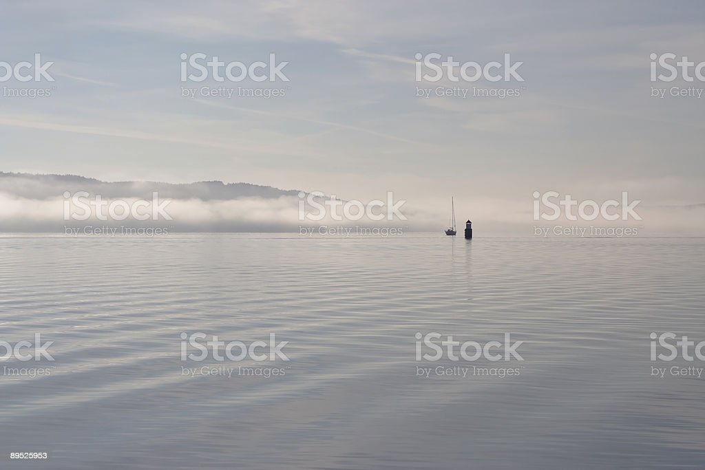 Sailboat and lighthouse in fog II stock photo