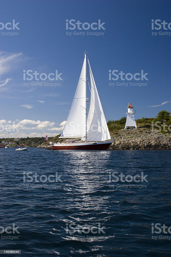 Sailboat and lighthouse. stock photo
