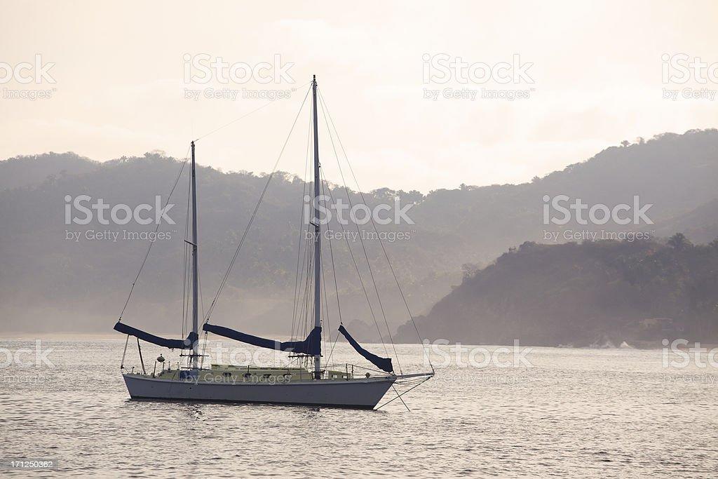 Sailboat at Dawn on Foggy Morning stock photo