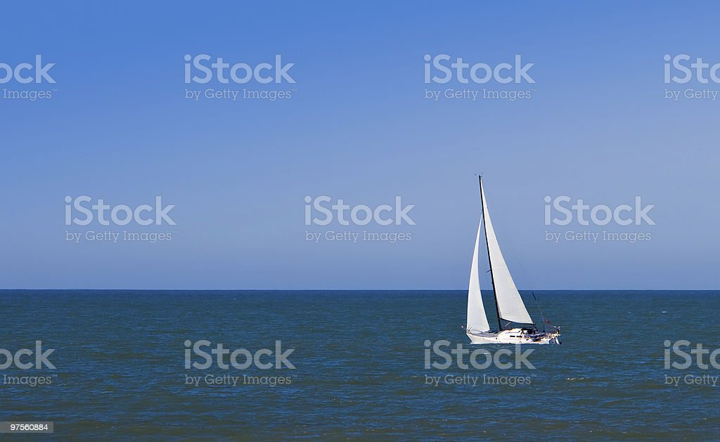 Sailboat at sea against clear, blue sky. royalty-free stock photo