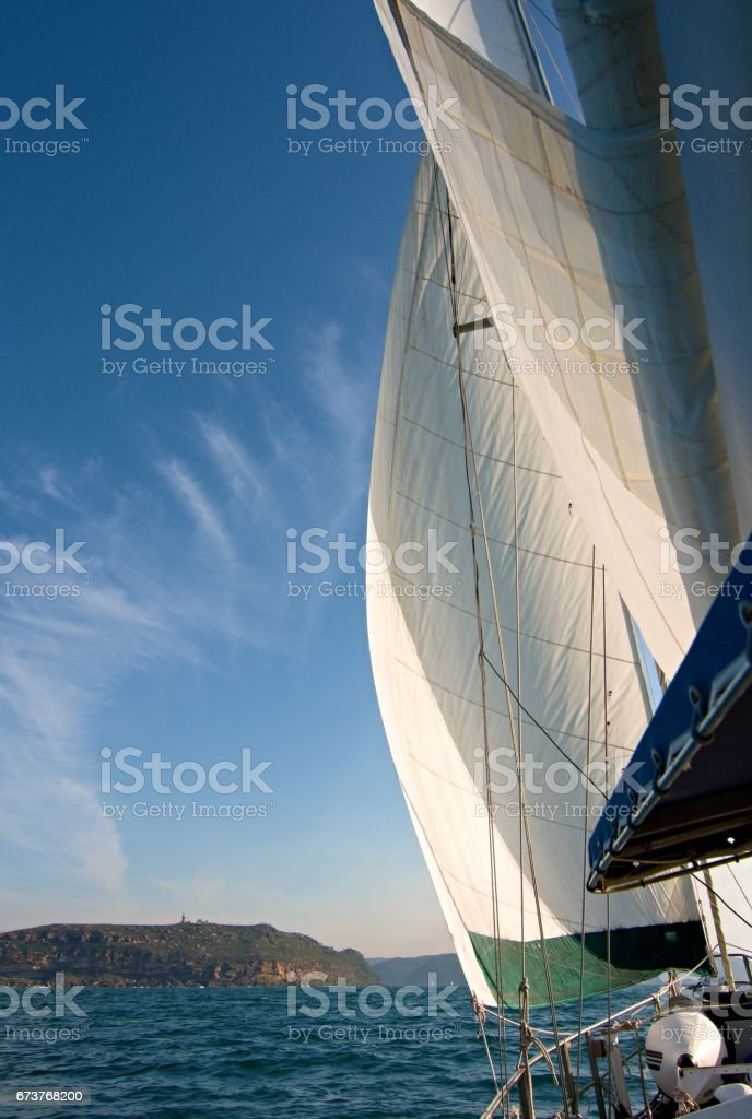 Sailboat at Sea Under Full Sail with Landfall in the distance. stock photo