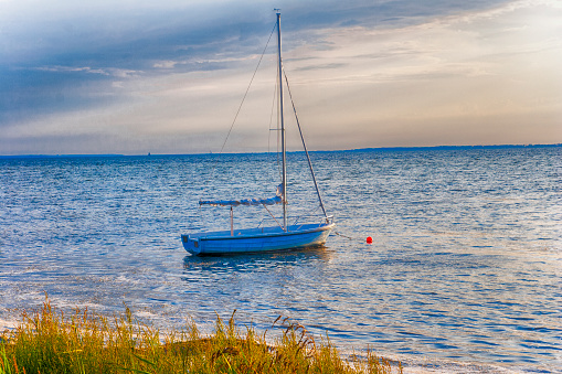 Sailboat at sunset moored on the beach