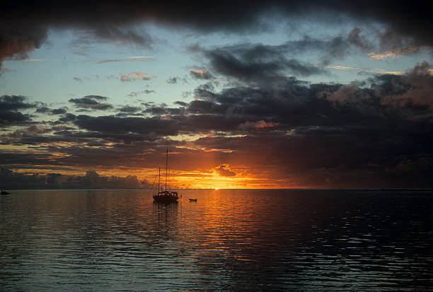 Sailboat at sunset, South Pacific A lone sailboat with brooding clouds and a tiny hint of the last piece of the sun as it is going down. hearkencreative stock pictures, royalty-free photos & images