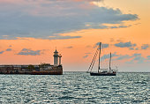 Sailboat at yellow sunset about lighthouse\nSailing. Yachting. Tourism. Yalta, Crimea