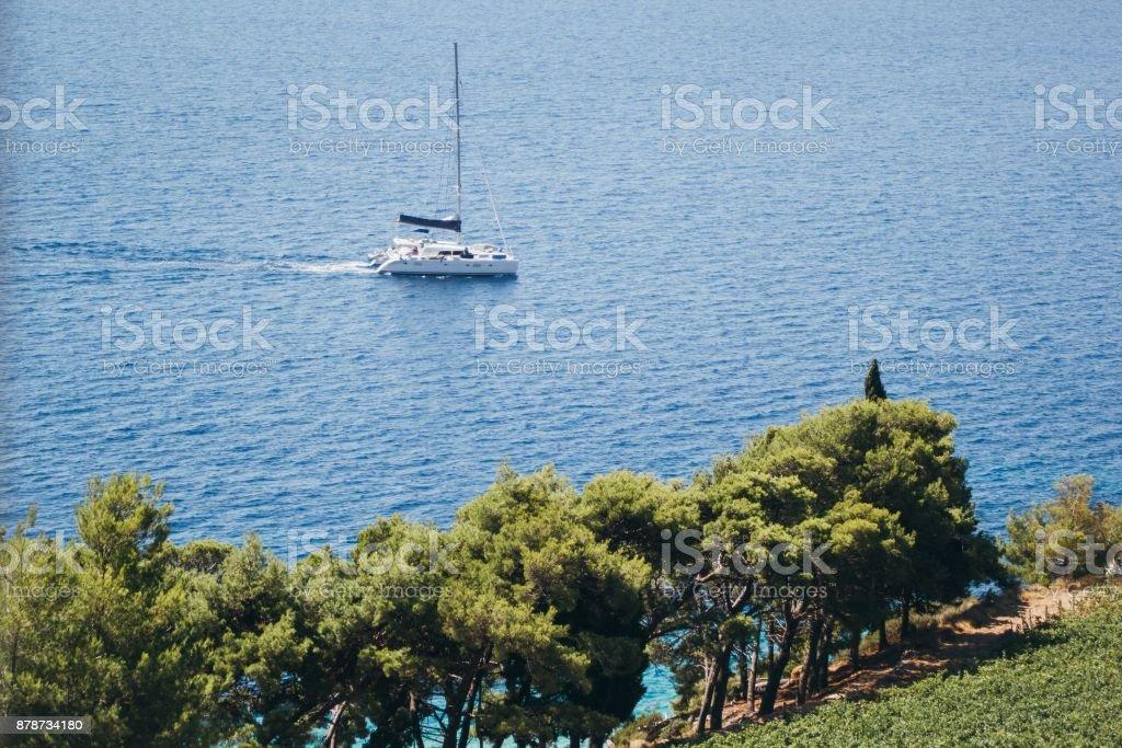 Sailboat catamaran on blue sea at coast of Croatia stock photo