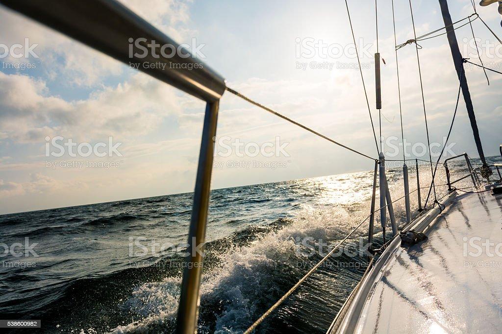 Sailboat creating splash on the open sea stock photo