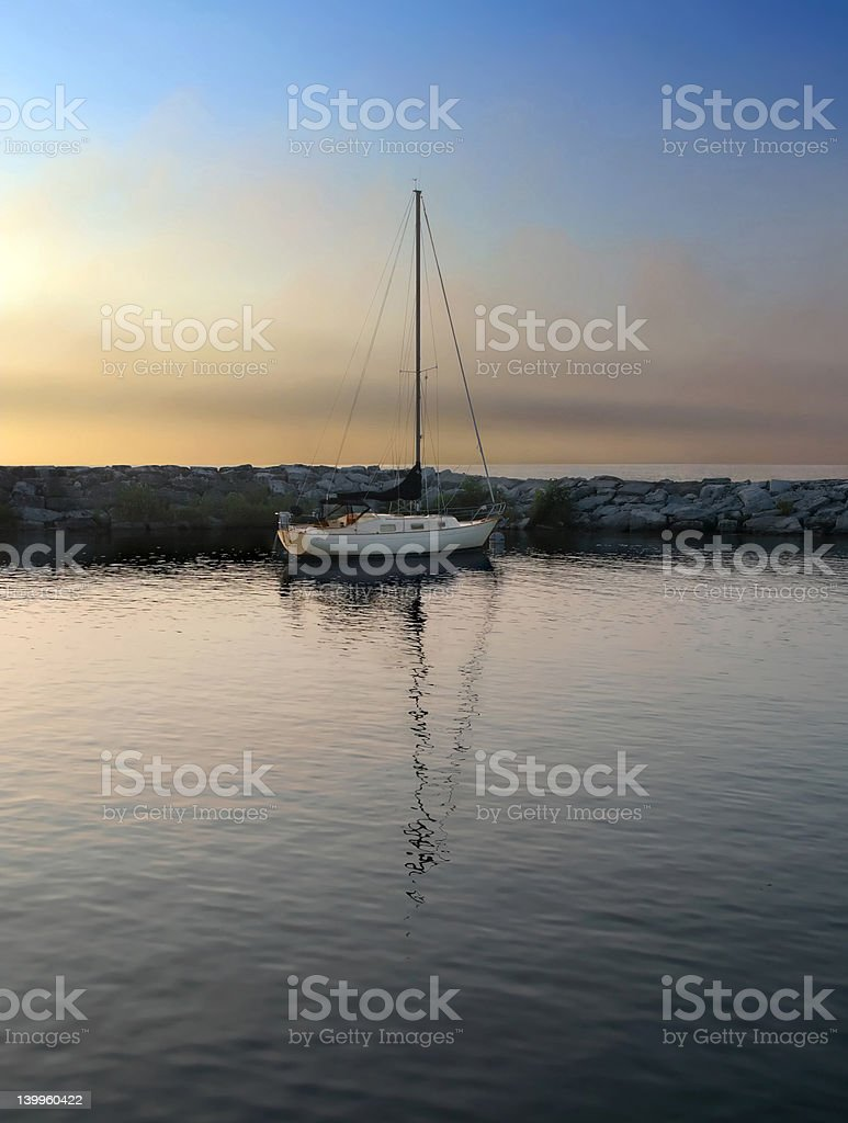 Sailboat in harbor at sundown stock photo