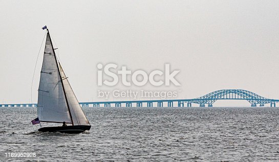 An individual is sailing in his sailboat moving toward the Robert Mosses Bridge in the Great South Bay Babylon New York off of Long Island.