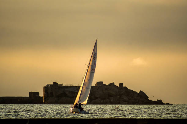Sailboat in the harbor of Cherbourg during sunset. Normandy, France Cherbourg-Octeville, France - August 22, 2018: Sailboat in the harbor of Cherbourg during sunset. Normandy, France cherbourg stock pictures, royalty-free photos & images
