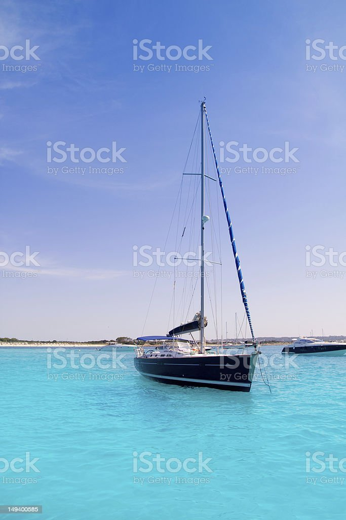sailboat in turquoise beach of Formentera stock photo