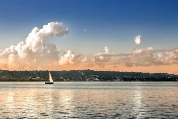 Sailboat in waters of Lake San Roque at sunset, Villa Carlos Paz, Cordoba, Argentina. stock photo