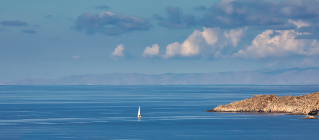 Single white sailboat sailing  in the mediterranean travelling towards Zia island in Greece. Stock Image.