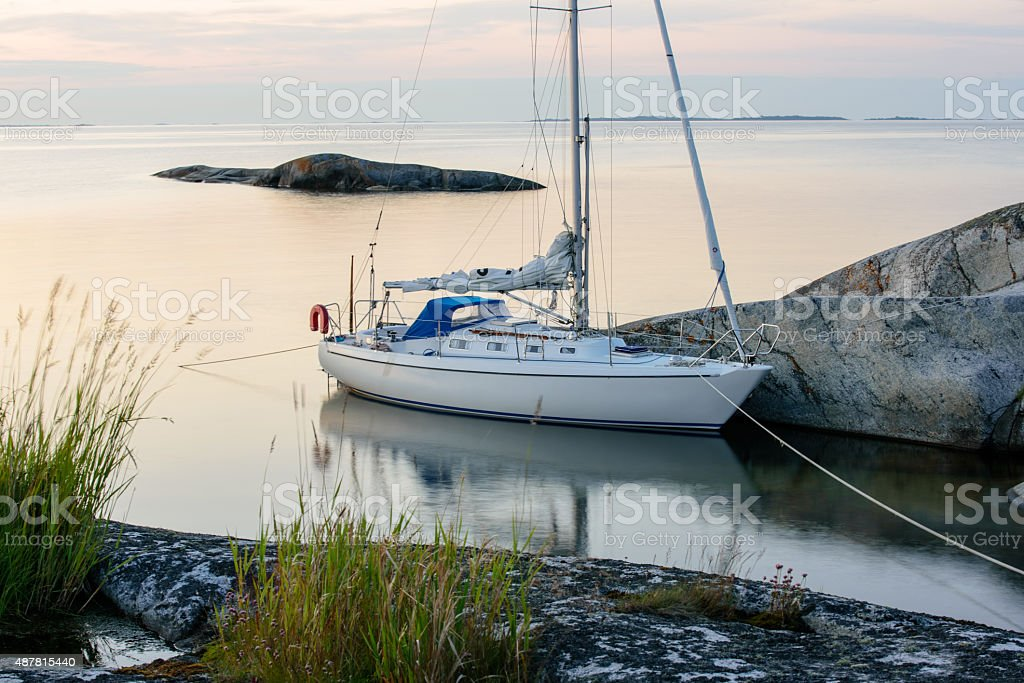 Sailboat moored long side a small rocky island stock photo