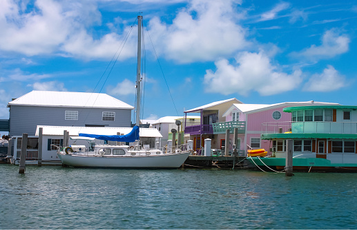 A sailboat moored near colorful houseboats at a marina near Key West.