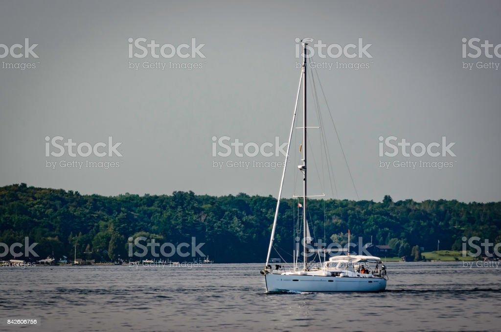 Sailboat motoring on the St. Lawrence River with the Upper New York State treed shoreline in the background. stock photo