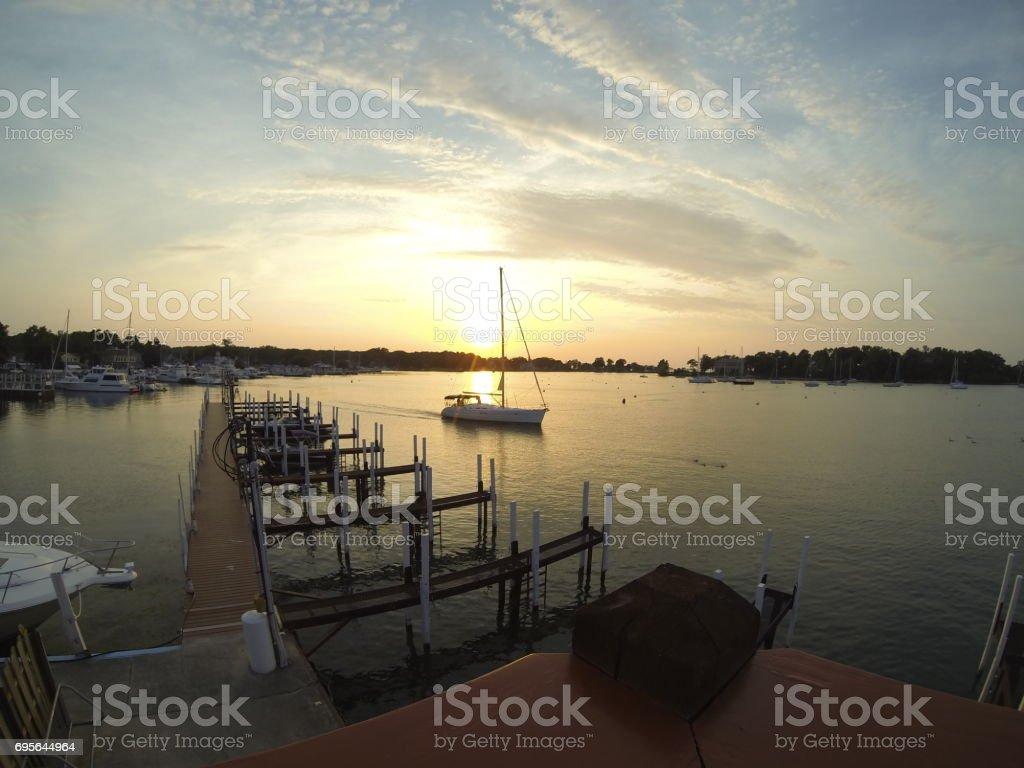 sailboat motoring out to bay stock photo