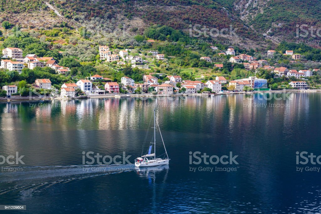 Sailboat Motoring Past Kotor Village stock photo