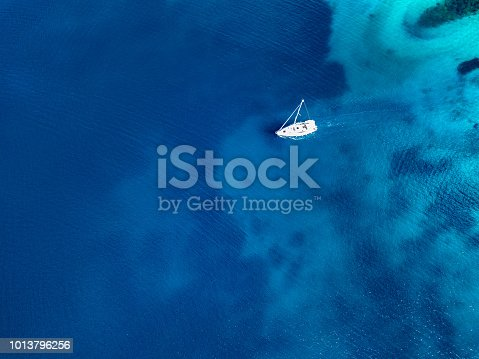 Sailboat during cruising with motor. High angle view photo from drone DJI Mavic Pro.