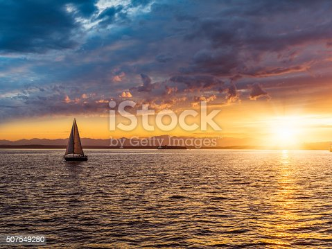 Sailboat on Elliott Bay in sunset, Seattle, WA, USA.