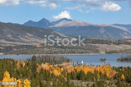 With yellow aspen and pine trees covering the hillsides, a sailboat cruises the waters of Lake Dillon or Dillon Reservoir in Summit County. The 14,000+ foot mountains of Grays (on the right) and Torreys Peaks (pyramid shaped peak in the middle rise into a blue autumn sky.
