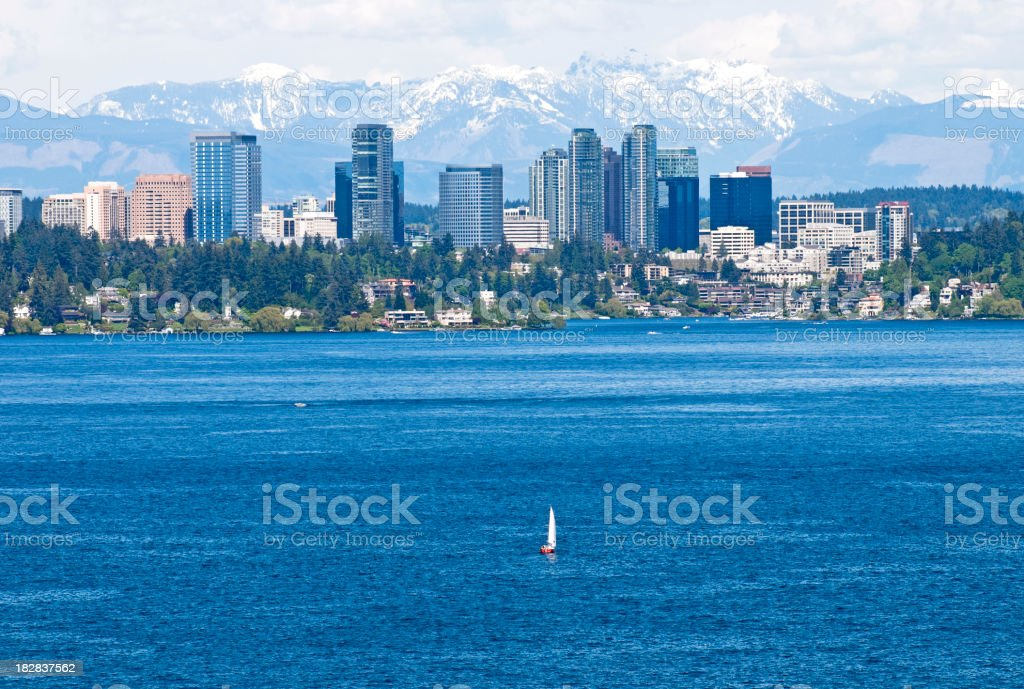 Sailboat on lake in front of city stock photo