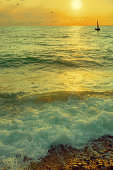 Sailboat sailing on the black sea at sunset. Waves lapping the rocky shore. Golden sunset in the reflection of the waves.