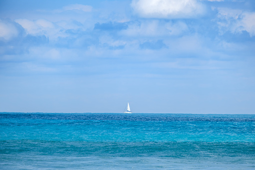 A lone white sailboat sits on the vast blue horizon in the Atlantic Ocean.