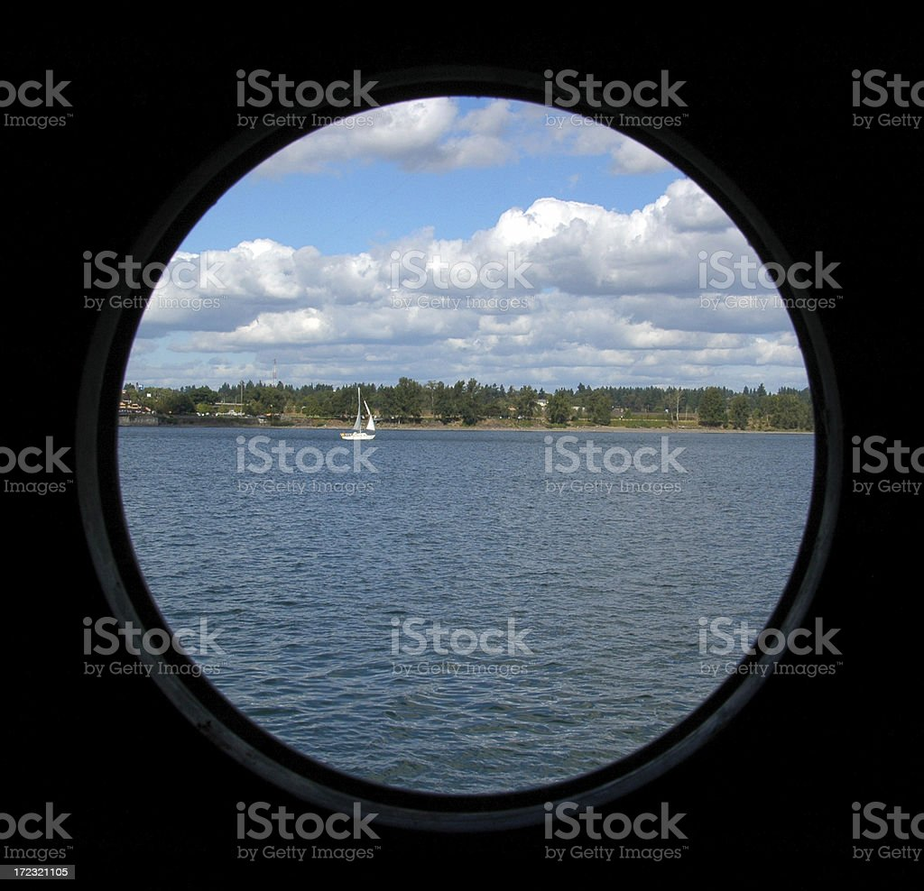 Sailboat on the River though a Porthole royalty-free stock photo
