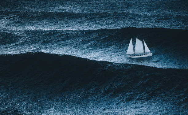sailboat on the sea with storm and big waves stock photo