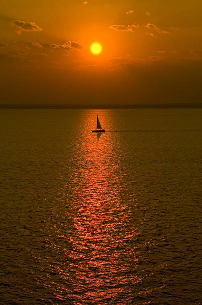 Sailboat out at sea during sunset stock photo