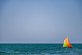 A Sailingboat sailing alone in the middle of huge a peaceful ocean, rising its colorful sails to allow the wind give its gently energy.