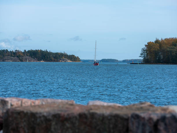 A Sailboat sailing between two islands in the Finnish archipelago. stock photo