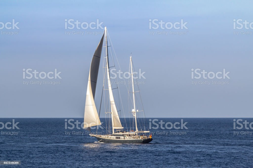 Sailboat sailing in the evening stock photo