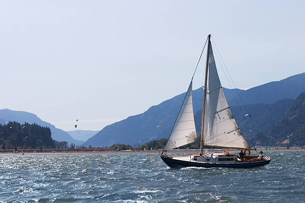 Sailboat Sailing on Water with Mountains in Background Sailboat on water with mountains in background.More of my sports images: hood river valley stock pictures, royalty-free photos & images