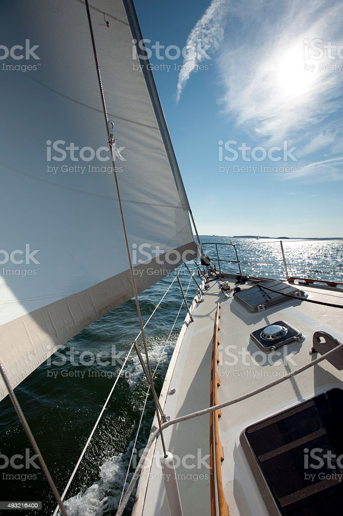 Sailboat sailing towards the horizon stock photo
