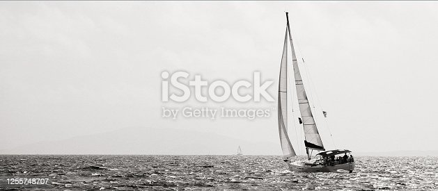 A high-contrast, black-and-white image of a sailboat in the British Virgin Islands with room for text on the left side of the frame.