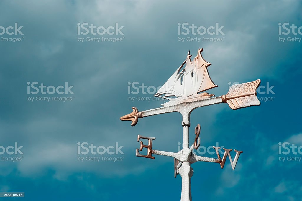 Sailboat wind vane against blue sky with copy space stock photo