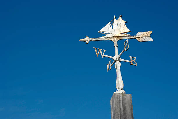 Sailboat wind vane against clear sky with copy space Low angle view of sailboat wind vane against clear sky with copy space. weather vane stock pictures, royalty-free photos & images