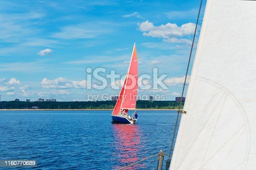 four men are sailing on a sailboat with red sails on the lake against the backdrop of the shore with an urban landscape