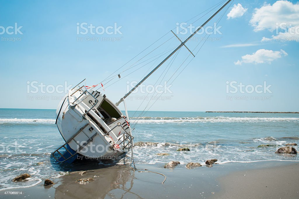 sailboat wrecked and stranded on the beach stock photo