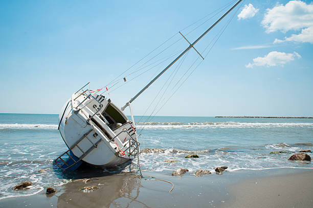 sailboat wrecked and stranded on the beach - stranded stock pictures, royalty-free photos & images