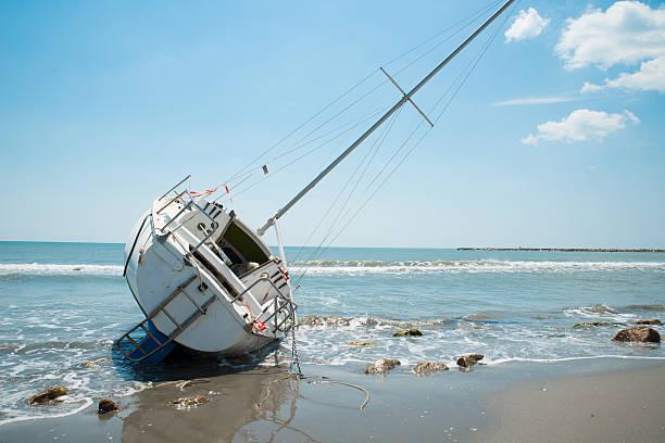 sailboat wrecked and stranded on the beach - grundstött bildbanksfoton och bilder