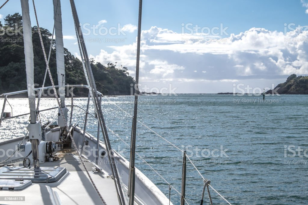 Sailboat yacht motoring out of Tutukaka Harbour between rocks and navigational channel marker in Northland, New Zealand, NZ stock photo