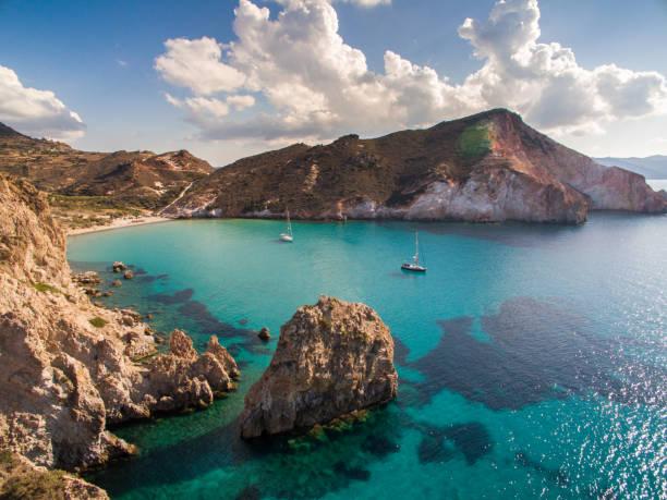 bateaux à voiles ancrés dans la baie à l'île de milos - grece photos et images de collection