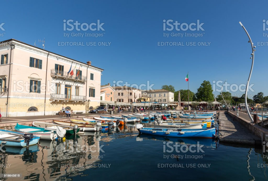 Sailboats and fishing boats at Porto di Bardolino harbor on The Garda Lake . Italy stock photo