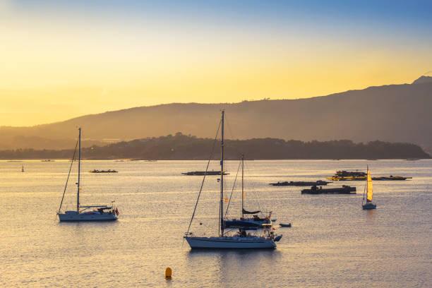 Sailboats and rafts at sunset stock photo