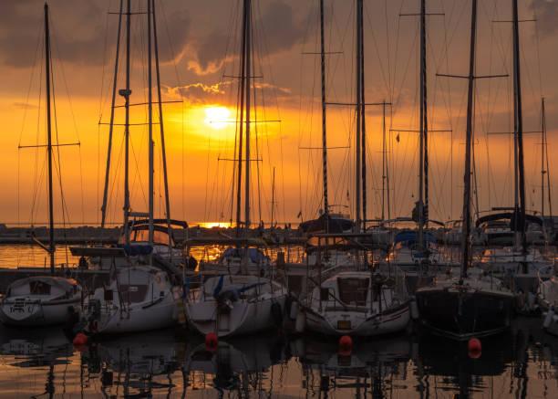 Sailboats at sunset stock photo