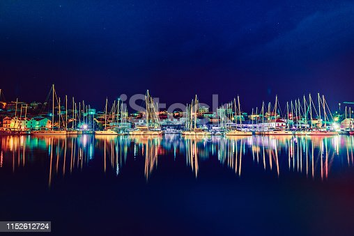 Sailboats in the harbor at clear night.